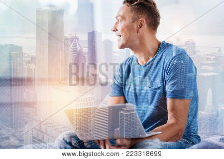 Express positivity. Dreamy male holding laptop and turning head while sitting against urban surrounding