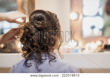 Unrecognizable girl back to us, young woman in  mirror at hairdresser  making hairstyle, styling  from  long hair in hair salon, partially visible  hands hairdresser master. Selective focus