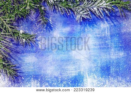 textured wooden blue background with white scrapes and scratches, left fir branches in the snow