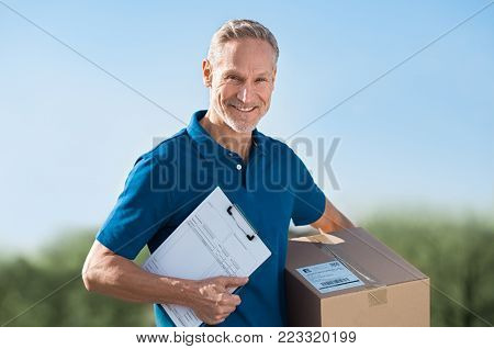 Smiling delivery man holding package and bill. Postman in blue uniform holding parcel and looking at camera. Happy courier man holding cardboard box and clipboard with delivery receipt.