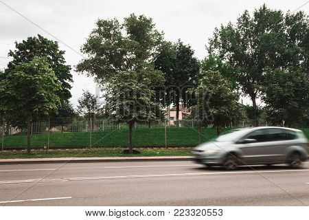 A grey car at high speed crosses a pedestrian crossing, a motion blur effect