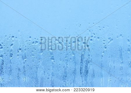 Humidity on a window with a blurred background. Texture of water droplets on glass