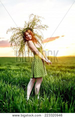 Beautiful girl in a green dress with wreath of flowers lay. Green meadow on sunset