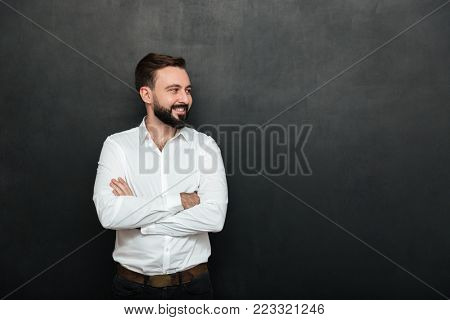Portrait of positive man in white shirt standing with arms folded and looking away over dark gray background copy space