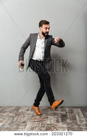 Full-length image of uptight man with takeaway coffee looking at watch being late and running along gray background