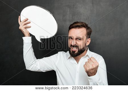 Close up photo of successful man holding blank speech bubble encouraging to be self-motivated and ambitious over dark gray wall copy space