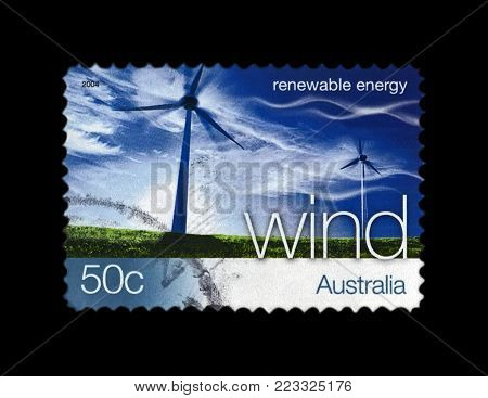 AUSTRALIA - CIRCA 2004: canceled stamp printed in Australia shows wind station on blue sky with clouds, wind renewable energy, circa 2004. vintage postal stamp isolated on black background.