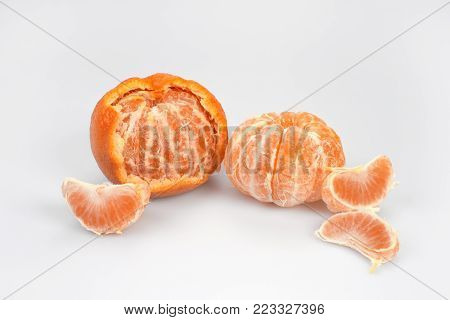 Two mandarins, peeled and peeled on a white background.