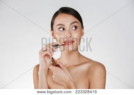 Beauty portrait of magnificent woman with healthy skin applying red lipgloss at her lips and looking away isolated over white background