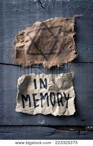 high angle view of a ragged jewish badge and a yellowish piece of paper with the text in memory written in it, on a gray rustic wooden surface