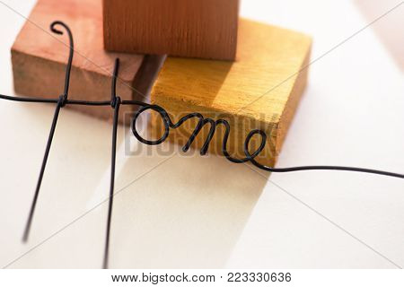 HOME made from black wire in front of brick or terracotta colored wooden blocks.