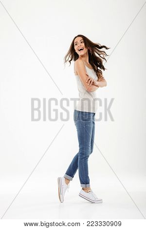 Full length image of Cheerful brunette woman posing sideways and looking back over gray background