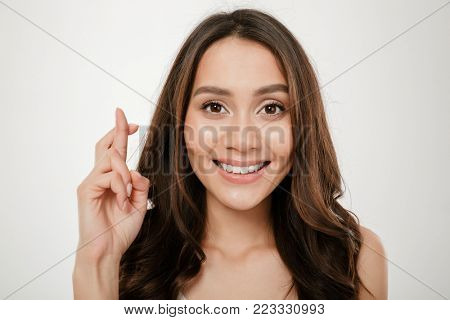 Close up portrait of smiling cute woman holding fingers crossed for good luck isolated over white background