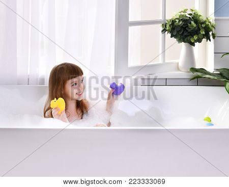 Happy little baby girl sitting in bath tub playing with duck toys in the bathroom. Portrait of baby bathing in a bath full of foam near window