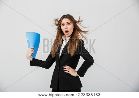 Portrait of a shocked businesswoman dressed in suit waving with a folder isolated over gray background
