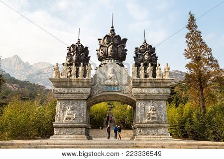 November 2015 - Qingdao, China - Chinese tourists under a beautiful carved archway at the entrance of Huayan temple in Na Luo Yan Ku, Laoshan Mountain