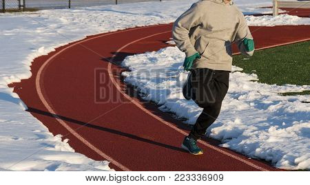 A track and field runner is sprinting on the shoveled lane of a track after it snowed the day before.
