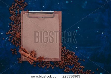 Blank wooden clipboard with craft paper in a header with coffee beans and spices. Creative food flat lay concept with copy space.