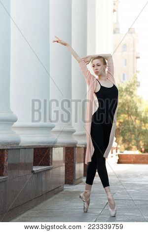 A ballet dancer in the pointe dance in the street. Performance on the city street. Slender female feet. Classical ballet.