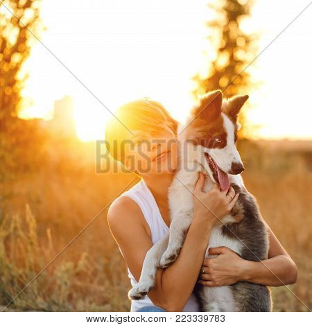 The girl is hugging her pet. Purebred Husky puppy. Love to the animals. Close-up portrait.