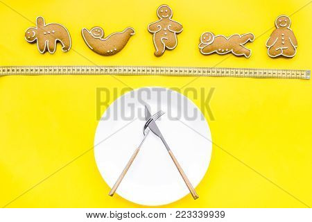 Proper nutrition for lose weight. Empty plate, apple and measuring tape on bright yellow background top view.