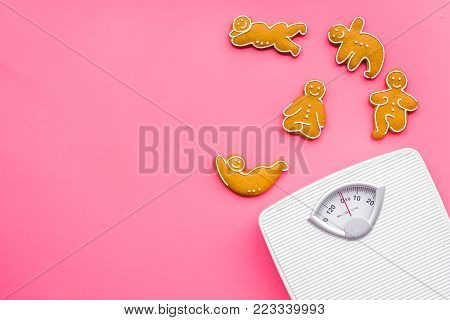 Ways for lose weight. Sport. Cookies in shape of yoga asans near scale on pink background top view.