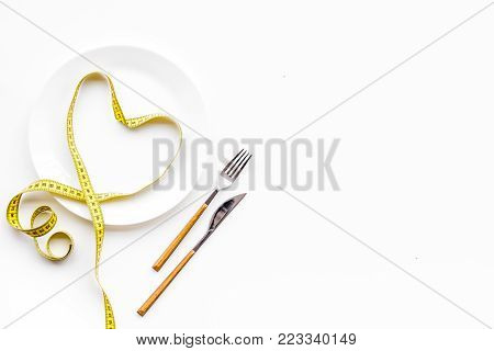 Medical starvation for lose weight. Empty plate and measuring tape on white background top view.