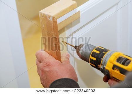 Installation of furniture hinges on the cabinet door master drills the door in the cabinet door