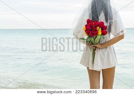 Beautiful bride holding a round bouquet of flowers at wedding day outdoors at ocean beach.