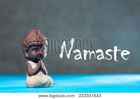 Close-up of little buddha meditating, focus on arms in Namaste gesture and text namaste - yoga and zen concept.