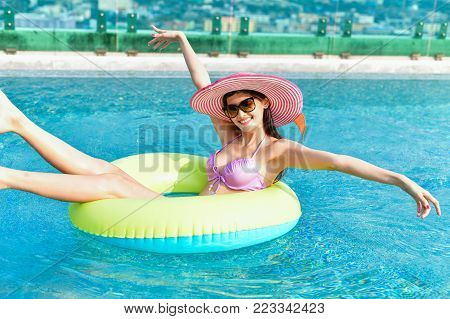 Swimsuit Concept. Beautiful girl wearing pink swimsuit. Beautiful girl in swimwear is relaxing at the swimming pool. Independent living sexy woman at the city center pool.