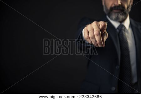 Angry senior man pointing his finger towards you, accusing and blaming you for incompetence