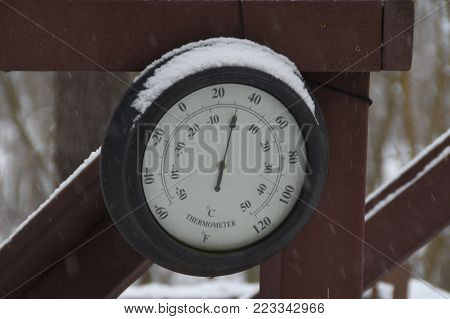 Round Circular Outdoor Thermometer Covered With Snow Shows Low Temperatures Near Zero. Low Temperatu