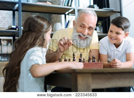 Family leisure time. Selective focus on a funny retired man and his grandson smiling cheerfully and looking at a cute little girl while all playing chess together.