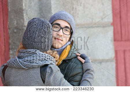 Young man hugging his beloved girlfriend outdoors