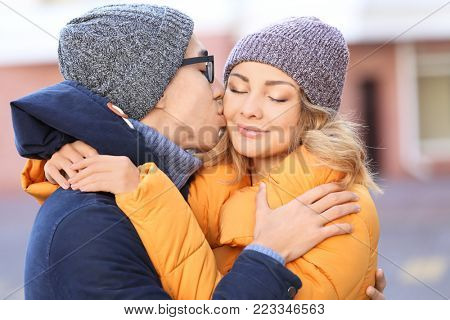 Young man kissing his beloved girlfriend outdoors