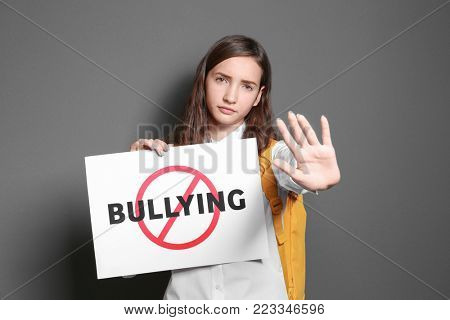 Teenage girl holding sign with crossed word