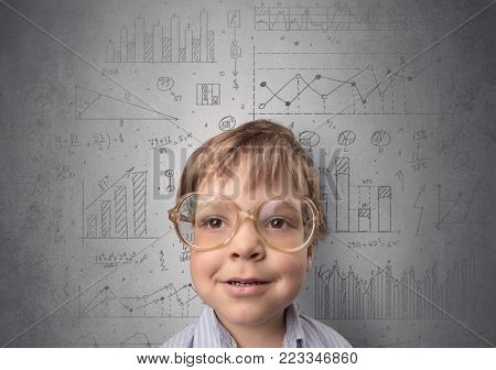Little boy in front of a grey wall with graphs and statistics around