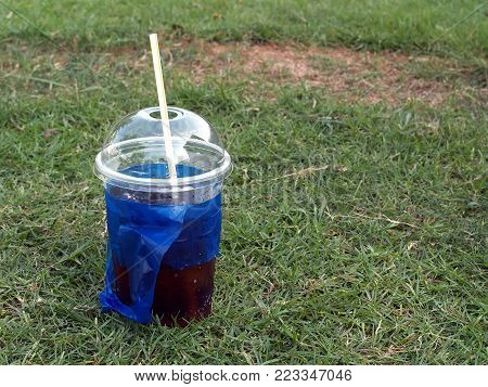 close-up soda pop in transparent plastic cup with white straw and blue bag on green grass field, cool refreshment carbonated drink and take away container