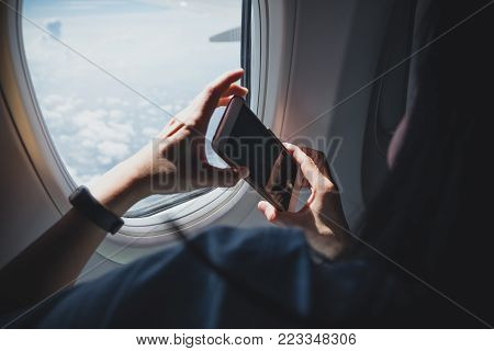 Close up woman hand holding mobile phone and take a photo outside airplane window