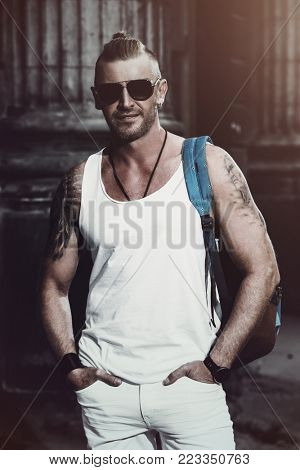 Masculine mature man with backpack standing on a city street. Sightseeing tours, travelling. Active lifestyle.