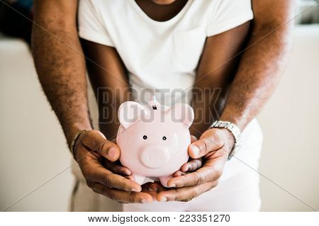 Dad and daughter holding piggy bank on hands