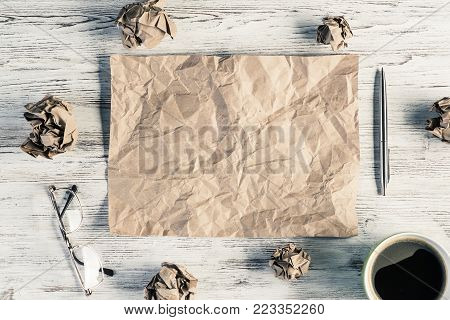 Top view of modern creative workplace with creased piece of sheet, pen, crumpled paper balls and cup of coffee placed on wooden table. Concept of finding of outstanding idea.