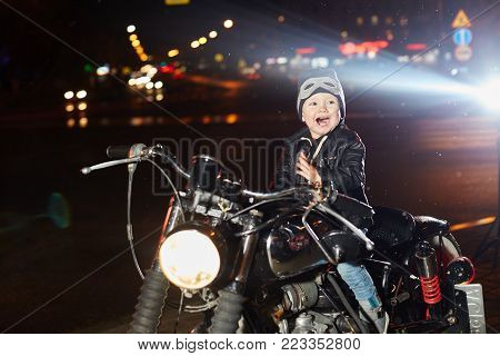 Kids Bikers On A Motorcycle Ride Through The City. The Young Biker Sitting On The Motorcycle And Smi