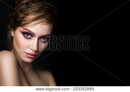 Closeup portrait of young beautiful woman with bright pink smokey eyes and lips over black background. Fashion makeup. Studio shot. Modern bright make up. Copy space