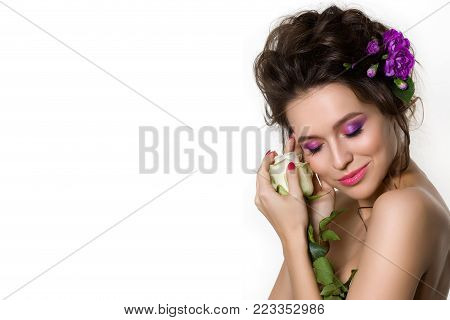Portrait of young beautiful woman with violet flowers in her hair posing over white background. Girl looking down and touching white rose. Bright summer fashion make up. Pink lips and smokey eyes.