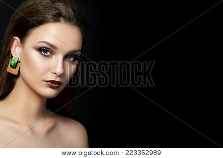 Close up portrait of young woman with brown lips and green smokey eyes over black background. Perfect eyebrows. Modern fashion make up. Studio shot. Copy space