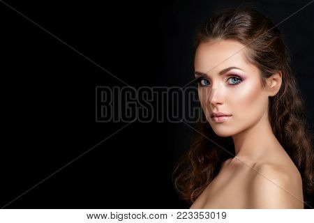 Close up beauty portrait of young pretty brunette model with multicolor smokey eyes make up posing over black background. Modern fashion make up. Studio shot