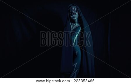 Beautiful young girl dressed in black shawl and mask with painted body stands against black background. Body art.