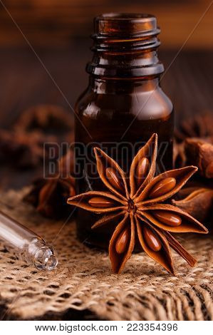 essential oil of the anise stars on a dark rustic background.